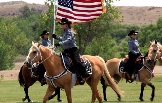 Officials Riding Horseback Carrying The American Flag [Courtesy/Fort Robinson State Park]
